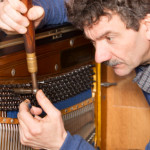 Piano Tuner working on upright piano